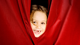 an image of a childs face peeping through stage curtains
